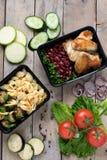 Twee plastic containers met geroosterde kippenvleugels en rauwe groenten op rustieke achtergrond, groentensalade royalty-vrije stock afbeeldingen