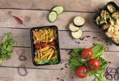Twee plastic containers met geroosterde kippenvleugels en rauwe groenten op rustieke achtergrond, groentensalade en micro- greens stock afbeeldingen