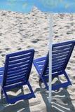 Twee plastic stoelen bevinden zich op strand onder paraplu Stock Afbeelding