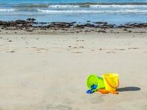 Twee plastic zandemmers met schoppen op een zandig strand Royalty-vrije Stock Foto's