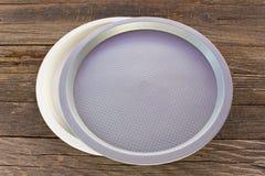 Twee platen van het middagmaal plastic ronde voedsel op houten achtergrond stock foto's