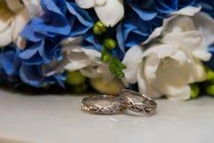 Twee platinatrouwringen liggen boeket van blauwe en witte bloemen Royalty-vrije Stock Afbeelding