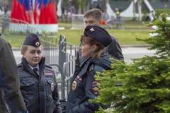 Twee politiemeisjes die op de straat met mensen spreken royalty-vrije stock fotografie