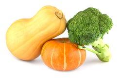 Twee pompoenen en broccoli Stock Foto