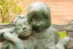 Twee poppen die op een bank zitten openlucht Royalty-vrije Stock Afbeeldingen