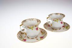 Twee porselein, decoratieve koppen met schotels op geïsoleerd wit Royalty-vrije Stock Afbeeldingen
