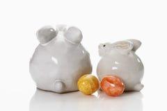 Twee porseleinpaashaas op witte achtergrond met geverfte paaseieren Royalty-vrije Stock Fotografie