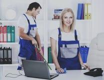 Twee portiers met het schoonmaken van materiaal in bureau stock fotografie