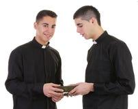 Twee priesters die een bijbel overgaan stock afbeeldingen