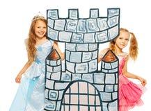 Twee prinsessen achter de toren van het kartonkasteel stock afbeeldingen