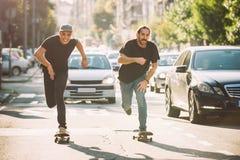 Twee pro de ritvleet van de skateboardruiter door auto's op straat royalty-vrije stock foto's
