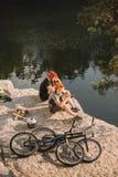 twee proeffietsers die dichtbij van de logboekenketel en berg cycli op rotsachtige klip rusten stock fotografie