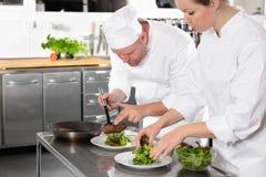 Twee professionele chef-koks bereidt lapje vleesschotel bij gastronomisch restaurant voor stock fotografie