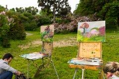 Twee professionele schilders die dichtbij hun sketchbooks in een pa zitten stock afbeeldingen