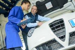 Twee professionele werktuigkundigen het inspecteren motor van een auto bij hun garage royalty-vrije stock afbeeldingen
