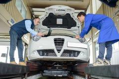 Twee professionele werktuigkundigen het inspecteren motor van een auto bij hun garage stock fotografie