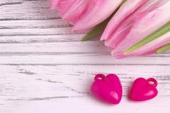 Twee purpere harten met roze tulpen op witte geschilderde rustieke witte houten achtergrond De dag van de valentijnskaart Royalty-vrije Stock Fotografie