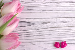 Twee purpere harten met roze tulpen op witte geschilderde rustieke witte houten achtergrond De dag van de valentijnskaart Royalty-vrije Stock Foto's