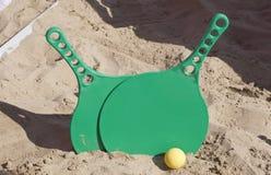Twee rackets en een bal op het zandige strand stock foto