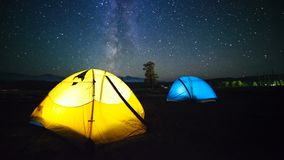 Twee reizigers die op de meteoordouche in de zomertijd letten Timelapse van sterren die zich in nachthemel bewegen over de kampte stock video