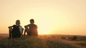 Twee reizigersjongen Twee jongens lopen langs het gebied bij zonsondergang met rugzakken Het concept familie en reis stock videobeelden