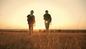 Twee reizigersjongen Twee jongens lopen langs het gebied bij zonsondergang met rugzakken Het concept familie en reis stock video
