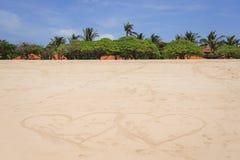 Twee reusachtige harten op een zandig tropisch strand Palmen, zand en blauwe hemel op de oceaan Royalty-vrije Stock Foto