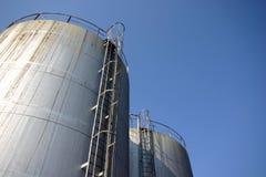 Twee reusachtige industriële silo's tegen een blauwe hemel Royalty-vrije Stock Afbeeldingen