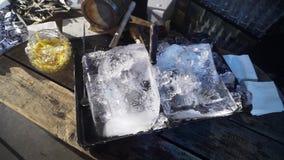 Twee reusachtige stukken van ijs met mes in zwart dienblad worden geplaatst op houten lijst stock video