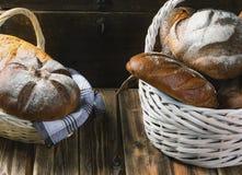 Twee rieten manden met vers brood op een houten lijst Stock Afbeelding