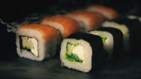 Twee rijen van sushi in een rookwolk, broodjes op een lei schepen met eetstokjes, voedselachtergrond, Japanse keuken in