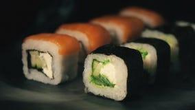 Twee rijen van sushi in een rookwolk, broodjes op een lei schepen, voedselachtergrond, Japanse keuken in