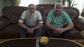 Twee rijpe hogere mensen die op de bruine leerbank zitten die op TV letten De vrienden leunen gelijktijdig vooruit, wachtend op stock videobeelden