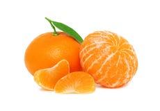 Twee rijpe mandarins en twee plakken met groene bladeren () Stock Afbeeldingen