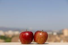 Twee rode appelen met stadsachtergrond Royalty-vrije Stock Foto's