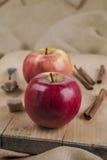 Twee rode appelen op houten raad en kruiden Stock Fotografie