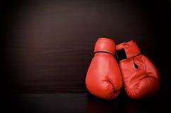 Twee rode bokshandschoenen aan de kant van het kader op een zwarte achtergrond Stock Fotografie