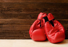 Twee rode bokshandschoenen aan een kant van het kader op een houten bruine achtergrond Royalty-vrije Stock Fotografie