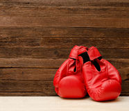 Twee rode bokshandschoenen aan een kant van het kader op een houten bruine achtergrond Royalty-vrije Stock Afbeeldingen