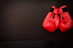 Twee rode bokshandschoenen die op een zwarte achtergrond in de hoek van het kader hangen Stock Foto's