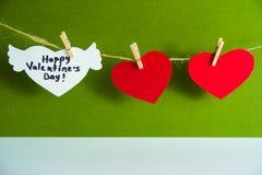 Twee rode document harten en één wit hart met gelukwens en vleugels vast met wasknijpers op een koord op groen Stock Afbeeldingen