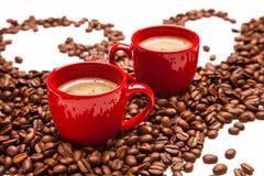 Twee rode espressokoppen met koffiebonen Stock Afbeeldingen