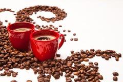 Twee rode espressokoppen met koffiebonen Royalty-vrije Stock Afbeeldingen