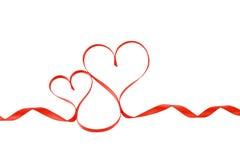 Twee rode geïsoleerder harten van het satijnlint, stock afbeelding
