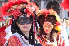 Twee rode gemaskeerde vrouwen in Carnaval van Venetië Stock Fotografie
