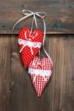 Twee rode harten die over houten achtergrond hangen royalty-vrije stock afbeelding