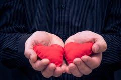 Twee rode harten gehouden mannelijke handen royalty-vrije stock foto