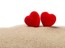 Twee rode harten in het zand op een wit royalty-vrije stock foto