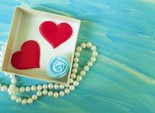 Twee rode harten, houten blauwe achtergrond, rode romantische doos, parels, bloemen Royalty-vrije Stock Foto's