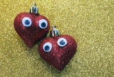 Twee rode harten in liefde met ogen in heldere gouden als achtergrond Royalty-vrije Stock Afbeeldingen